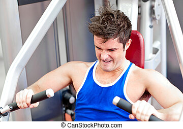 Muscular young man using a bench press in a fitness center