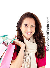 Joyful woman wearing a scarf and holding shopping bags smiling at the camera against a white background
