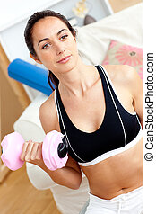 Serious athletic woman holding a dumbbell in her living-room...