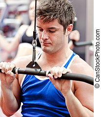 Beautiful young man using a bench press in a fitness center