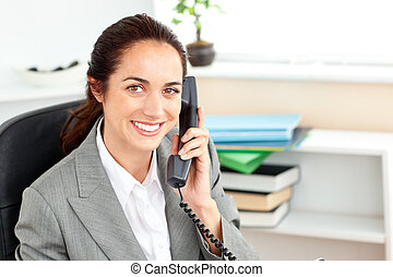 Positive businesswoman talking on phone sitting in her office