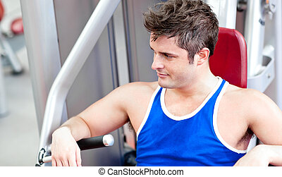 Relaxed young man using a bench press in a fitness center