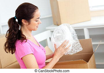 Young caucasian woman unpacking boxes with glasses
