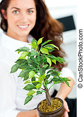 Smiling businesswoman holding a plant smiling at the camera