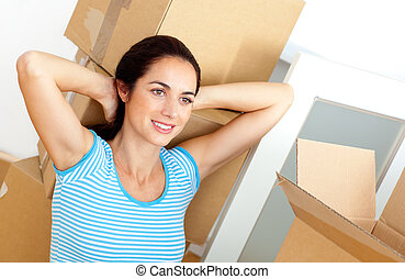 Relaxed young woman sitting on the floor after unpacking cardboards in her new house