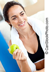 Smiling woman eating an apple on the sofa after working out in the living-room at home