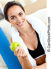 Radiant woman eating an apple on the sofa after working out in the living-room at home