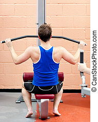 Assertive male athlete practicing body-building in a fitness...