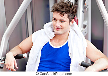 Attractive man with towel sitting on a bench press in a...