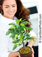 Glowing businesswoman holding a plant smiling at the camera