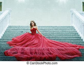 Young woman in a long red dress and gold crown sitting on the stairs.