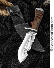 Hunting knife with a fishing net on a wooden table. -...