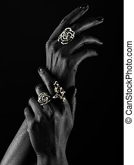 Dark-skinned hand with jewelry on a black background - Hands...