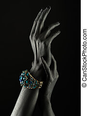 Dark-skinned hand with a gold bracelet on a black...