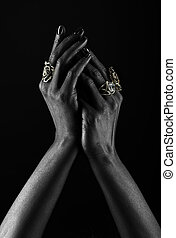 Dark-skinned hand with jewelry on a black background. Hands...