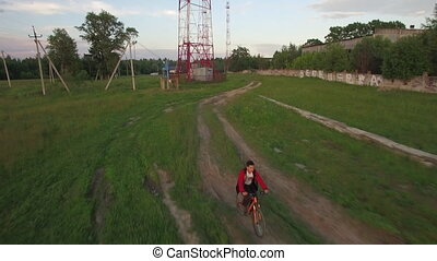 Aerial view of boy riding bike in the countryside - Aerial...