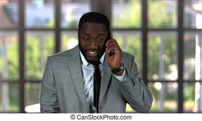Smiling businessman with phone. Happy black guy indoors. I...