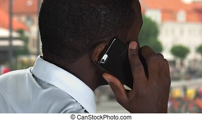 Phone talk in the street. Black man with a smartphone.