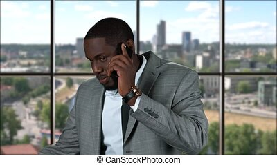 Black businessman with mobile phone. Smiling man on city...