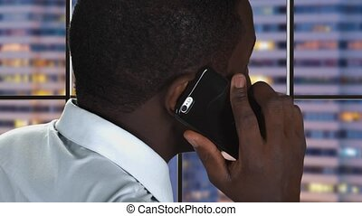 Black man speaking on phone. Guy on city evening background....