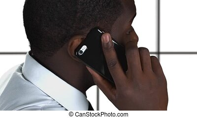 Phone talking on white background. Black guy holding...