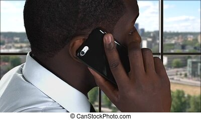 Phone talk on city background. Side view of black man....
