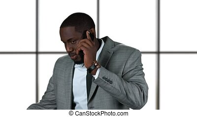 Afro-american businessman holding phone. Smiling man in suit...