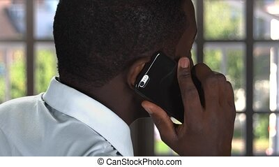Phone talk near the window. Black guy with a smartphone....