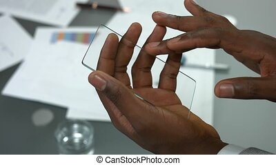 Transparent phone in male hands. Guy holding blank...