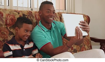 Father And Son Playing Game With Laptop Computer On Sofa -...