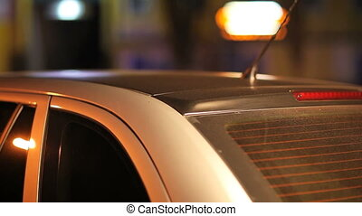 Night view of black roof of silver car