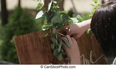 Decorator decorating welcome board with leafs