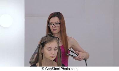 2 shots. Hairdresser using straightener on long hair of...