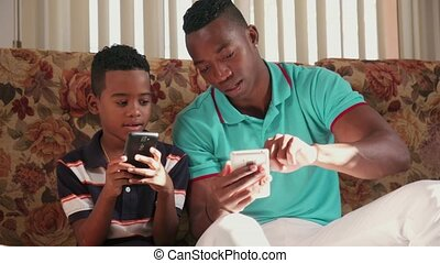 Black Man Teaching Mobile Telephone Technology To Boy At...