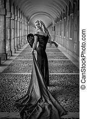 Angel, Beautiful blond woman in a black dress in the passage...