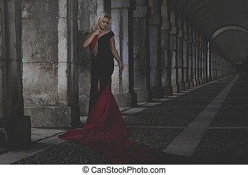 Beautiful blond woman in a black dress in the passage of a...