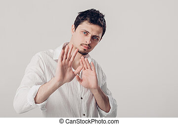 young man with dark hair in white shirt closed with hands on...
