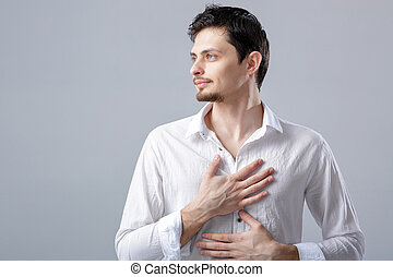 handsome young proud man in shirt holding hand on chest on...