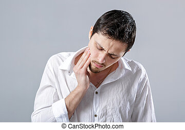 Frustrated young brunette man in shirt with toothache on...