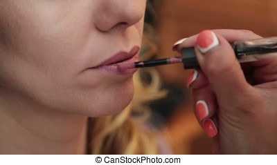 Makeup artist at work indoors with lipstick