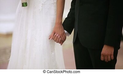 Bride and groom holding hands on ceremony indoors