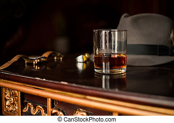 Glass of whiskey and men's watch on the wooden table