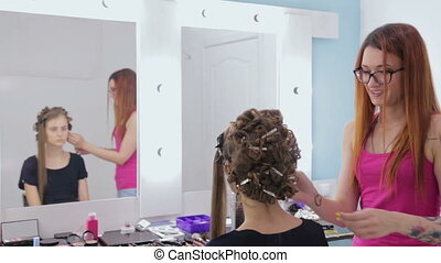 Hairdresser doing hairstyle for young pretty woman and using...