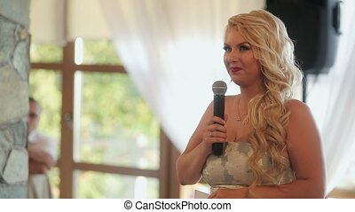Blonde young woman speaking in microphone on party