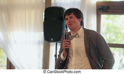 Brunette man speaking in microphone on party