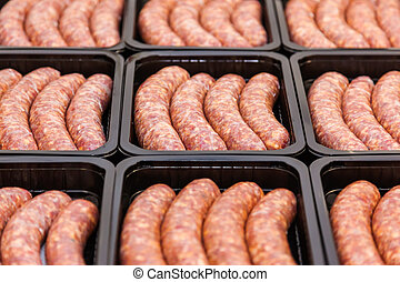 Raw meat sausages in packing box