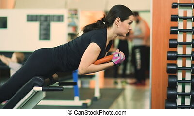 Strong brunette woman doing exercise in fitness club