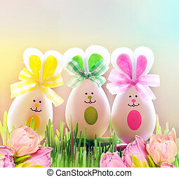 Colored easter eggs bunny on grass and flowers - Colored...