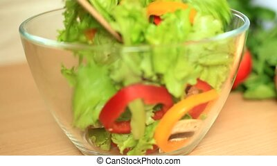 mixing diet salad with wooden spoons - mixing salad with...