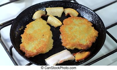 cooking potato pancakes in a frying pan with bacon